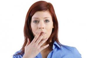 Frau hält sich verlegen die Hand vor den Mund
