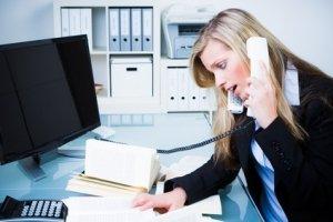 Junge Frau erschrocken am Telefon