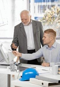 Junger Chef erklärt älterem Mitarbeiter etwas am PC